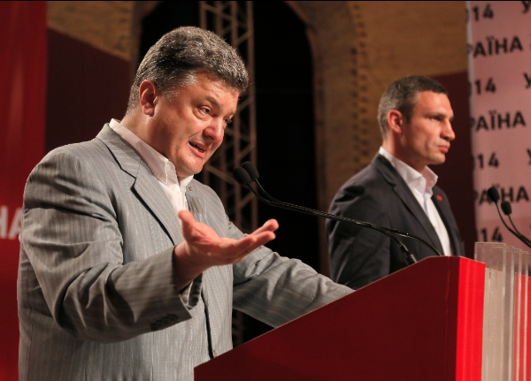 Ukrainian presidential candidate Petro Poroshenko, left, talks with Vitali Klitschko, at right, during a press conference, in Kiev, Ukraine, Monday, May 26, 2014 [AP]