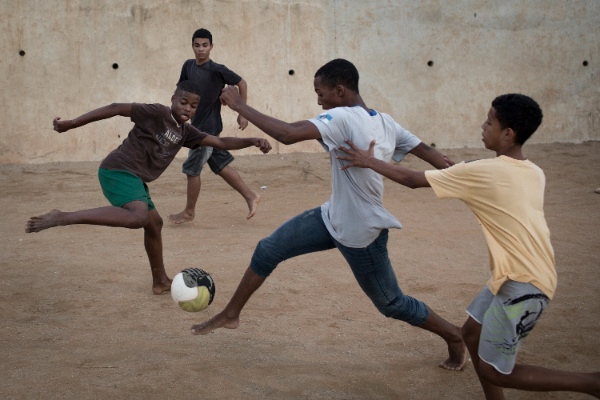 Young residents play soccer at the Sao Carlos slum in Rio de Janeiro, Brazil, Monday, May 12, 2014 [AP]