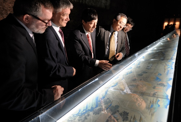 "Professor Lin Meicun(3rd R) from School of Archaeology and Museology of Peking University, introduces a 30-meter-long ancient Chinese map, depicting cities along the Silk Road, during the preview of ""To the East: Cities, Men and Gods Along the Silk Road"", the opening exhibition of the first Silk Road International Cultural Biennale, at the Baths of Diocletian in Rome, Italy, Oct. 20, 2011 [Xinhua]"