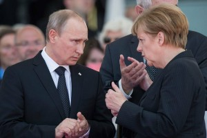Putin with German Chancellor Angela Merkel at the 70th anniversary of D-Day celebrations in France, June 6 2014 [PPIO]