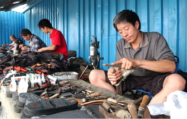 Chinese shoemakers work at the Russian-Chinese bazaar in Ussurisk, Russia, Sunday, Aug. 21, 2005. As China and Russia embark on a new stage of cooperation by holding joint military exercises launched from the Far East, the Chinese presence is slowly growing in this hard-scrabble region far from Moscow [AP]