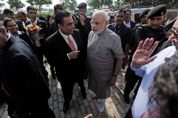 Chairman and Managing Director of Reliance Industries Limited Mukesh Ambani, center left, speaks with Gujarat state Chief Minister Narendra Modi in Gandhinagar, in the western Indian state of Gujarat, Saturday, Oct. 19, 2013 [AP]