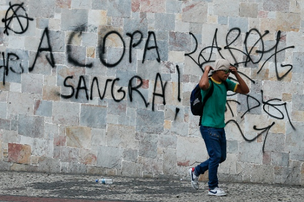 """A protester walks by a graffiti that reads in Portuguese """"the Cup bleeds,"""" during a demonstration against the 2014 World Cup in Belo Horizonte, Brazil, Thursday, June, 12, 2014 [AP Images]"""