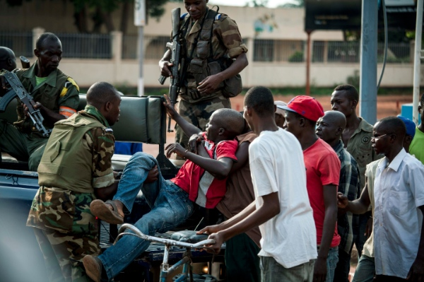 African Union Misca forces from Cameroon carry a wounded man as angry youth set up barricades throughout the town, Thursday May 29, 2014 in Bangui, Central African Republic [AP]