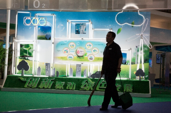 A cleaner walks past a display depicting clean energy sources at an energy conservation and environment protection exhibition in Beijing Monday, June 9, 2014. A Chinese environmental group launched a smartphone app on Monday that tracks and shames polluting factories, highlighting how the country is making environmental data more available and is welcoming public monitoring of companies that pollute [AP]