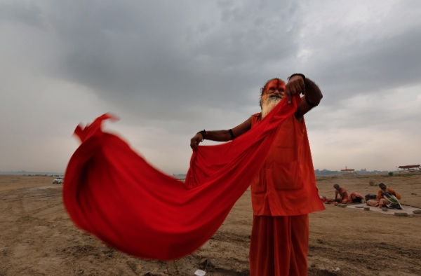A Hindu devotee dries his cloth after taking ritualistic holy dip at Sangam, the confluence of rivers the Ganges and the Yamuna in Allahabad, India, Tuesday, June 17, 2014 [AP]