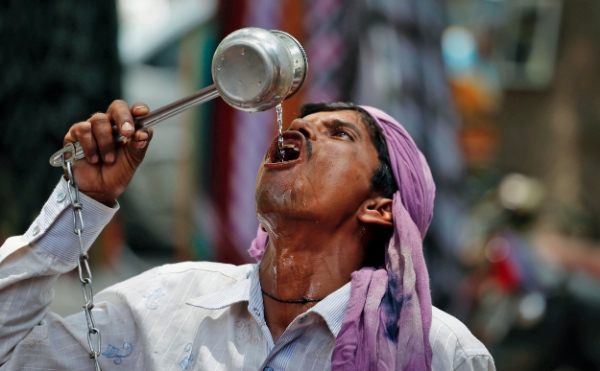 An Indian cycle rickshaw puller drinks water on a hot day in Allahabad, India, Saturday, June 7, 2014. Thousands of people enraged by power cuts during an extreme heat wave have been rioting across northern India, setting electricity substations on fire and taking power company officials hostage, officials said Saturday [AP]