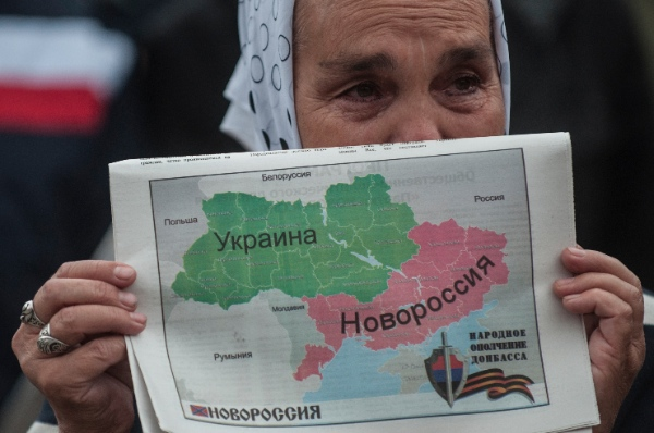 A woman holds a map of Ukraine divided into two parts, the eastern carrying the name Novorossia, or New Russia, during a rally in support of peace in Donetsk, eastern Ukraine, Wednesday, June 18, 2014. Hundreds of miners went on a protest walk through the streets of central Donetsk on Wednesday, trying to express support for a peaceful resolution to the eastern Ukraine conflict, ongoing for almost four months [AP]