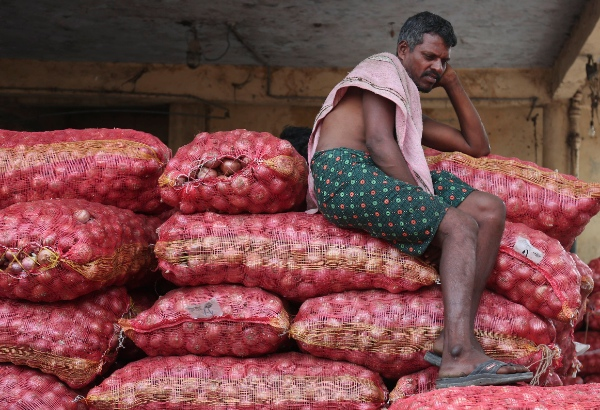 An Indian laborer rests on bags of onion at a wholesale market in Hyderabad, India, Saturday, June 21, 2014. Prices for onions, a diet staple in South Asia, have rised in recent weeks due to hostile weather conditions causing fall in supply [AP]