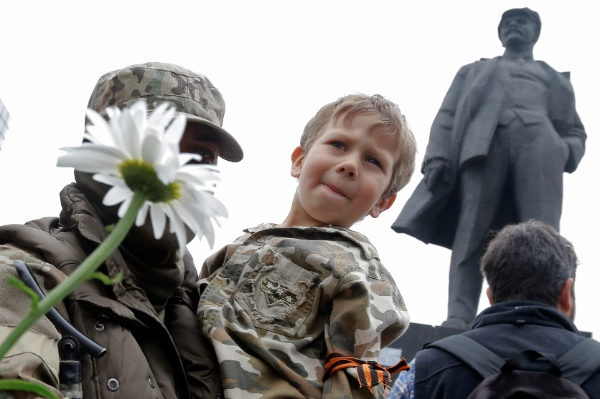A pro-Russian fighter holds a boy on his hands after taking an oath in Donetsk, eastern Ukraine Saturday, June 21, 2014, with a statue of Soviet Union founder Vladimir Lenin on the right [AP]