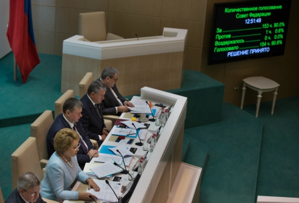 Speaker of Federation Council members Valentina Matviyenko, second left, looks at the screen in front of her during the voting in the Russian parliament's upper chamber in Moscow, Russia, Wednesday, June 25, 2014. On Russian President Vladimir Putin's demand, the upper house of Russian parliament on Wednesday canceled a resolution allowing the use of military in Ukraine [AP]