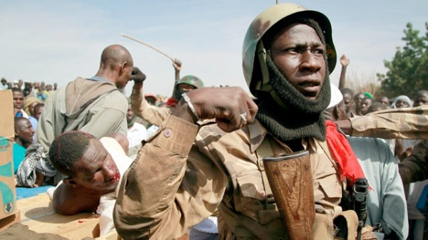File photo of Malian soldiers guarding suspected Islamist extremists after throwing them in the back of the army truck in Gao, northern Mali [AP]