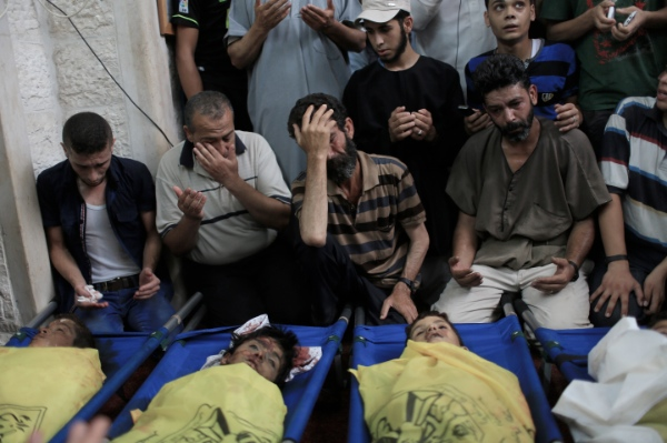 Palestinians gather around the bodies of the boys of Baker family, at a mosque before their funeral in Gaza City, on July 16, 2014 [Xinhua]