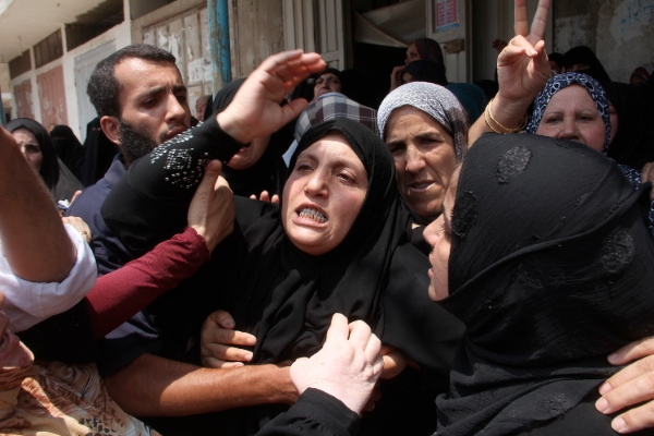 Relatives of the three Palestinian siblings of the Moamer family, who were killed in an Israeli airstrike, mourns during their funeral in the southern Gaza Strip city of Rafah on July 20, 2014 [Xinhua]