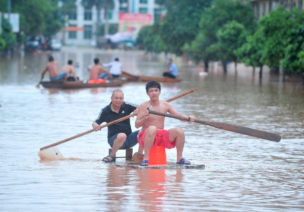 Local residents row out on a flooded road after landfall of the typhoon Rammasun in Ningming County, south China's Guangxi Zhuang Autonomous Region, July 21, 2014 [Xinhua]