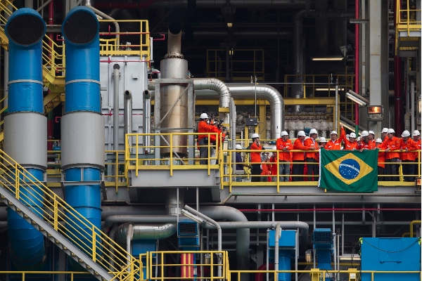 File photo of Brazil's President Dilma Rousseff, center right, arm raised, with workers at the Petrobras P-56 oil platform in Angra dos Reis, Brazil. The offshore platform, with a capacity of 100,000 barrels per day, was constructed entirely in Brazil, costing 1.5 billion dollars in 2011 [AP]