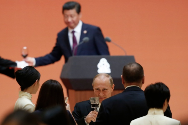 Russian President Vladimir Putin, center bottom, and Chinese President Xi Jinping, center top, toast at a gala dinner ahead of the fourth Conference on Interaction and Confidence Building Measures in Asia (CICA) summit, in Shanghai China, Tuesday, May 20, 2014 [AP]