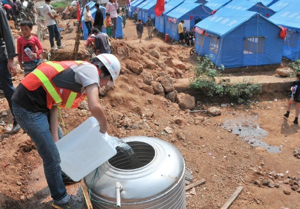 A staff member from Yunnan Construction Group adds direct drinkong water to a water tank in a temporary settlement after a 6.5-magnitude earthquake in Ludian County of Zhaotong, southwest China's Yunnan Province, Aug. 6, 2014 [Xinhua]