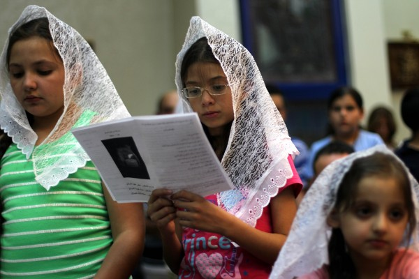 Hundreds of thousands of Christians, Mandeans and other minorities have fled Iraq since the 2003 US invasion. These Iraqi Christian girls attend a prayer service at a church in Amman, Jordan July 30, 2014 [Xinhua]