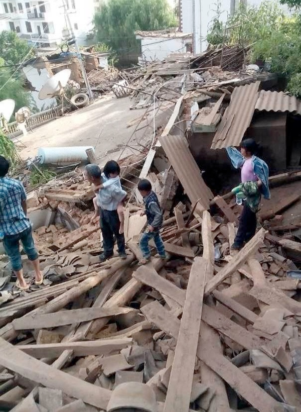 This photo taken by cellphone on Aug. 3, 2014 shows people standing on a damaged house after an earthquake in Ludian County of Zhaotong City in southwest China's Yunnan Province [Xinhua]