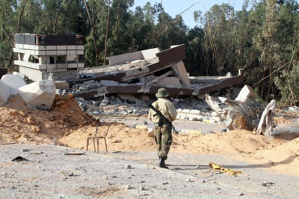 A soldier surveys an army barracks destroyed by artillery shelling in Tripoli [Xinhua]