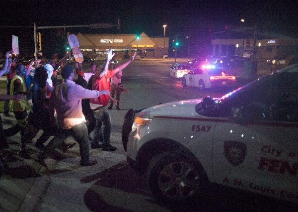 Protesters chase away a police vehicle during a demonstration in Ferguson, Missouri, the United States, on Aug. 15, 2014 [Xinhua]