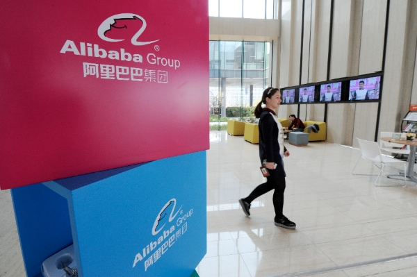 An employer walks past exhibition boxes printed with the logo of Alibaba Group in the Taobao City of Alibaba Group in Hangzhou, capital of east China's Zhejiang Province, March 25, 2014 [Xinhua]