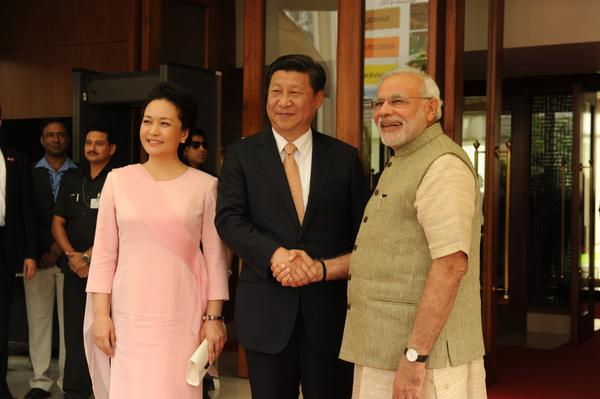 Prime Minister Narendra Modi (R) and China's President Xi Jinping (C) shake hands as Xi's wife Peng Liyuan looks on before their meeting in the capital city of Ahmedabad, in Gujarat, India on 17 September 2014 [MEA, India]