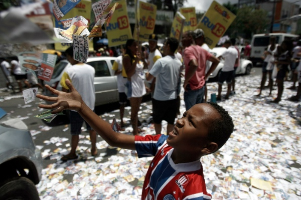 A boy plays with campaign flyers during the general elections in Salvador de Bahia, Brazil, on Oct. 5, 2014 [Xinhua]