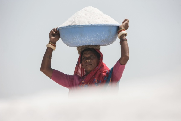 A laborer carries raw salt at an ancient salt field in Devla-Nada area of the state of Gujarat, India, May 1, 2014 [Xinhua]