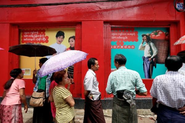 People wait to buy Ooredoo low-priced SIM card outside a SIM cards selling shop in Yangon, Myanmar, Aug. 4, 2014 [Xinhua]
