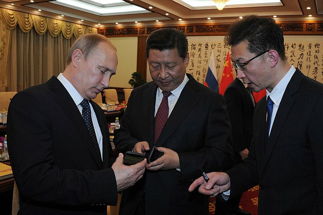 Putin (left) presented Chinese President Xi Jinping (center) with a Russian smartphone– a Yotaphone-2, with Russian, Chinese and APEC symbols uploaded for the occasion [PPIO]