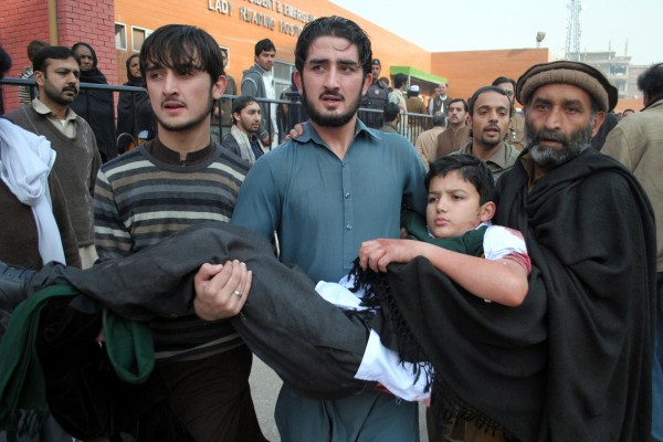 Volunteers hold an injured boy at a hospital in northwest Pakistan's Peshawar after six Taliban fighters stormed a school and killed at least 130 people [Xinhua]