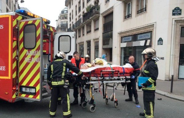 Firefighters carry an injured man on a stretcher in front of the offices of the French satirical newspaper Charlie Hebdo in Paris on January 7, 2015 [Xinhua]
