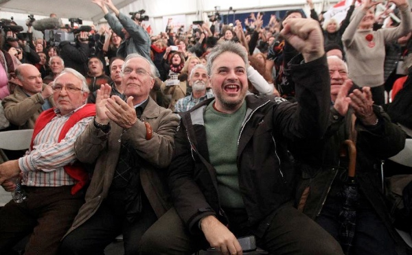 People react as they watch the exit poll results at the election kiosk of Left SYRIZA party in Athens, Greece, Jan. 25, 2015 [Xinhua]