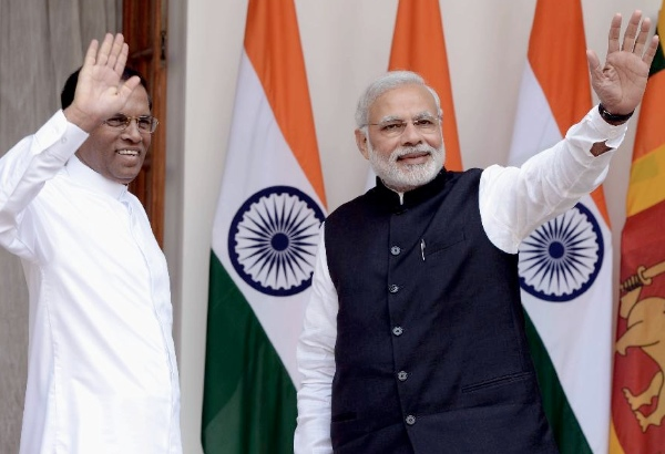 Sri Lankan President Maithripala Sirisena (L) and Indian Prime Minister Narendra Modi wave their hands before a meeting at Hyderabad House in New Delhi, India, Feb. 16, 2015 [Xinhua]