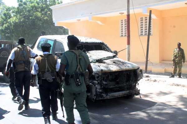 Somali soldiers inspect a car damaged in the attacks which killed at least 20 people in the capital Mogadishu Friday [Xinhua]