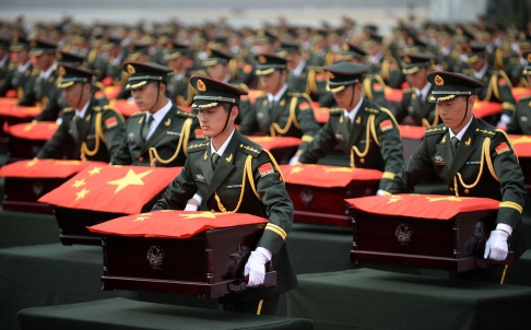 File Photo: People's Liberation Army soldiers accept caskets containing the remains  of 437 Chinese soldiers killed in the Korean war [Xinhua]