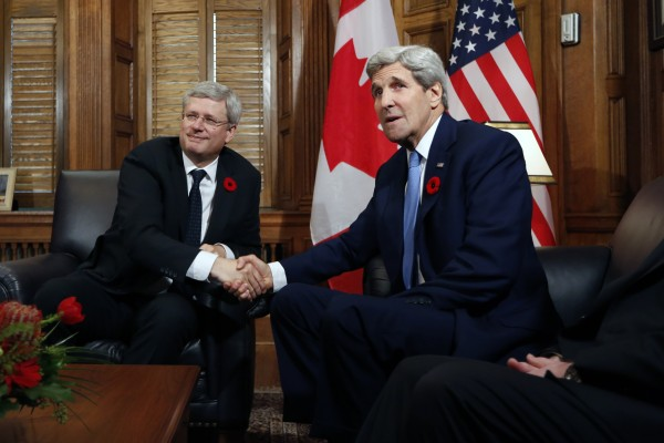 Harper greeting US Secretary of State John Kerry. Both Washington and Ottawa have provided military trainers and air support to combat ISIL in Iraq [Xinhua]