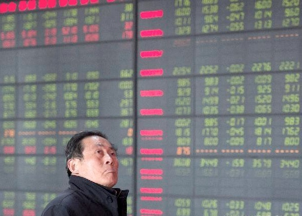 An investor looks through stock information at a trading hall of a securities firm in Hefei, capital of east China's Anhui Province, Dec. 9, 2014 [Xinhua]