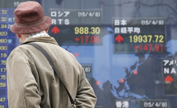 A man looks at an electronic board showing the stock index in Tokyo, Japan, April 9, 2015 [Xinhua]