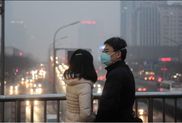 People wearing respirators are seen on a pedestrian bridge in downtown Beijing, capital of China, Feb. 22, 2014 [Xinhua]