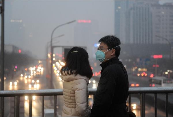 People wearing respirators are seen on a pedestrian bridge in downtown Beijing, capital of China, Feb. 22, 2014 [Xinhua]