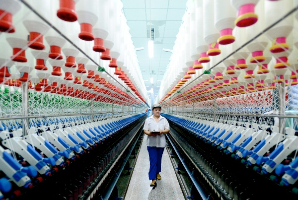 A labourer works at a spinning mill in Xiajin County, east China's Shandong Province, June 12, 2014 [Xinhua]