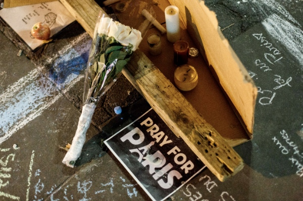 """A posters reading """"Pray for Paris"""" and flowers are placed at Union Square by mourners for Paris attacks in New York, the United States, Nov. 14, 2015 [Xinhua]"""