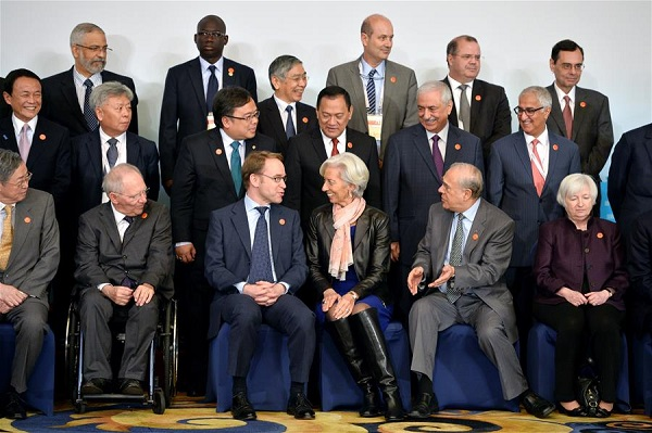 International Monetary Fund Managing Director Christine Lagarde (3rd R, front) talks with Germany's Federal Bundesbank chief Jens Weidmann (3rd L, front) before they pose for a family photo at the G20 Finance Ministers and Central Bank Governors Meeting at the Pudong Shangri-la Hotel in Shanghai, east China, Feb. 27, 2016 [Xinhua]