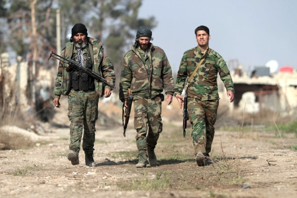 Syrian soldiers walk through territory seized from Islamist extremists in the town of Daraya, which does not fall under the ceasefire deal [Xinhua]