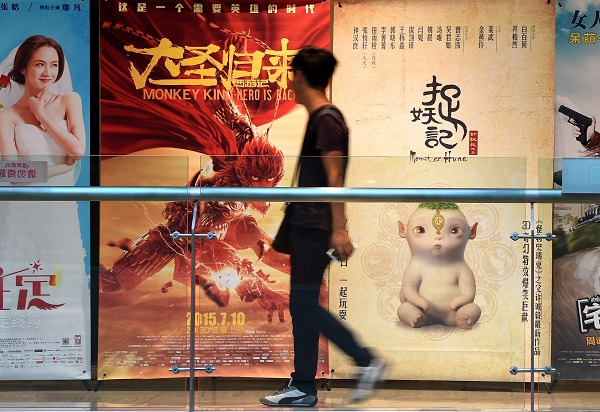 "A man walks past a poster of the ""Monster Hunt"" (R) at a cinema in Shenyang, capital of northeast China's Liaoning Province [Xinhua]"