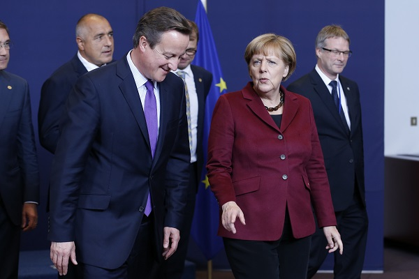 German Chancellor Angela Merkel (R, center) and British Prime Minister David Cameron (L, center) talk during a family photo session at the start of an EU Summit in Brussels, Belgium, Oct. 15, 2015 [Xinhua]